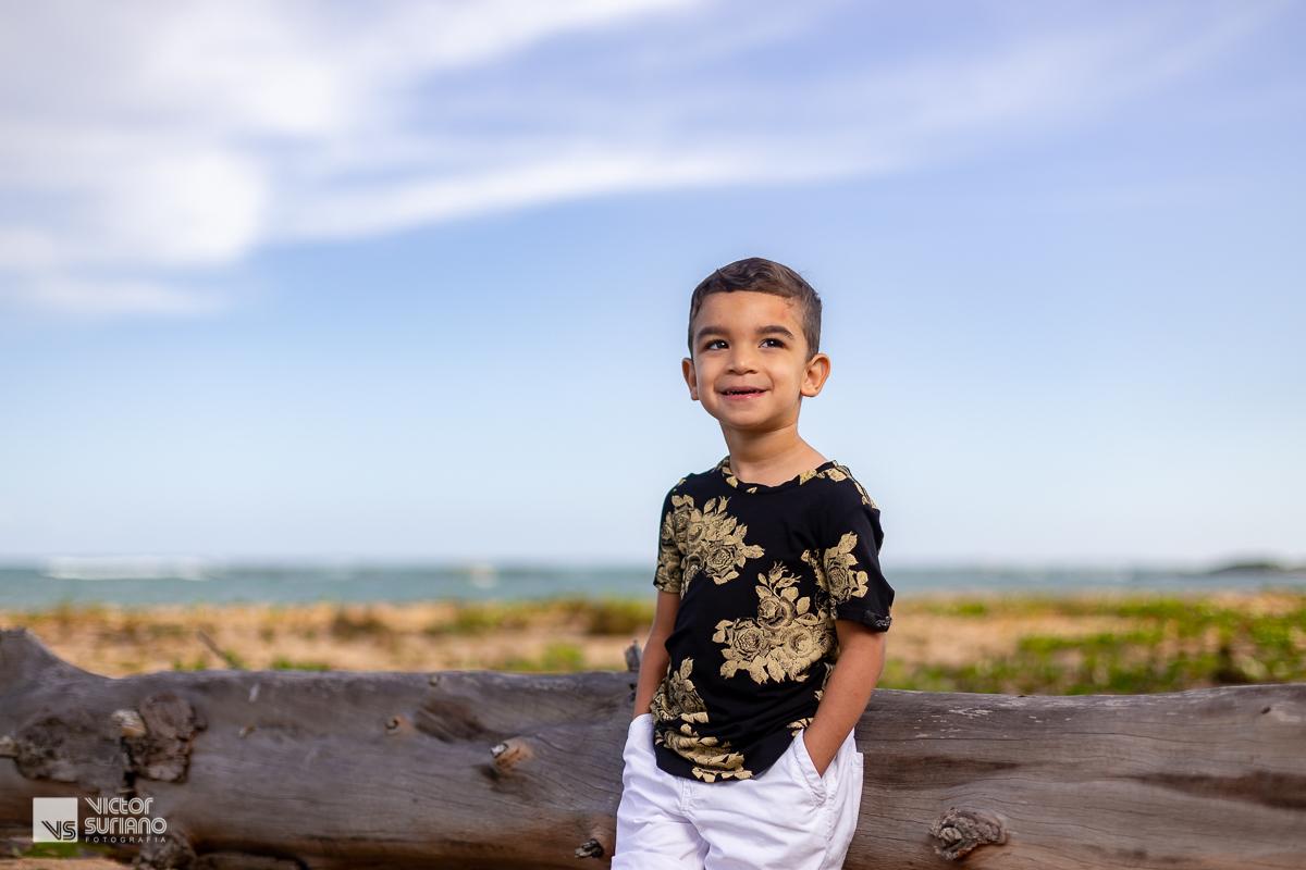 criança com as mãos no bolso e camisa preta com detalhe dourado