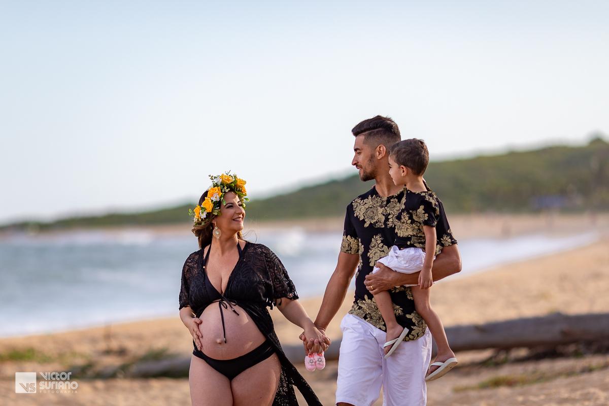 papai com filho no colo de mãos dadas com a esposa grávida na beira da praia em rio das ostras