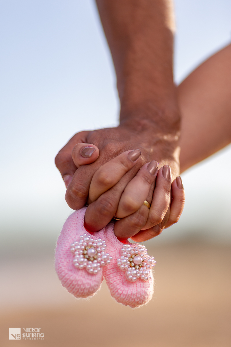 casal de mãos dadas e segurando o sapatinho rosa da bebê