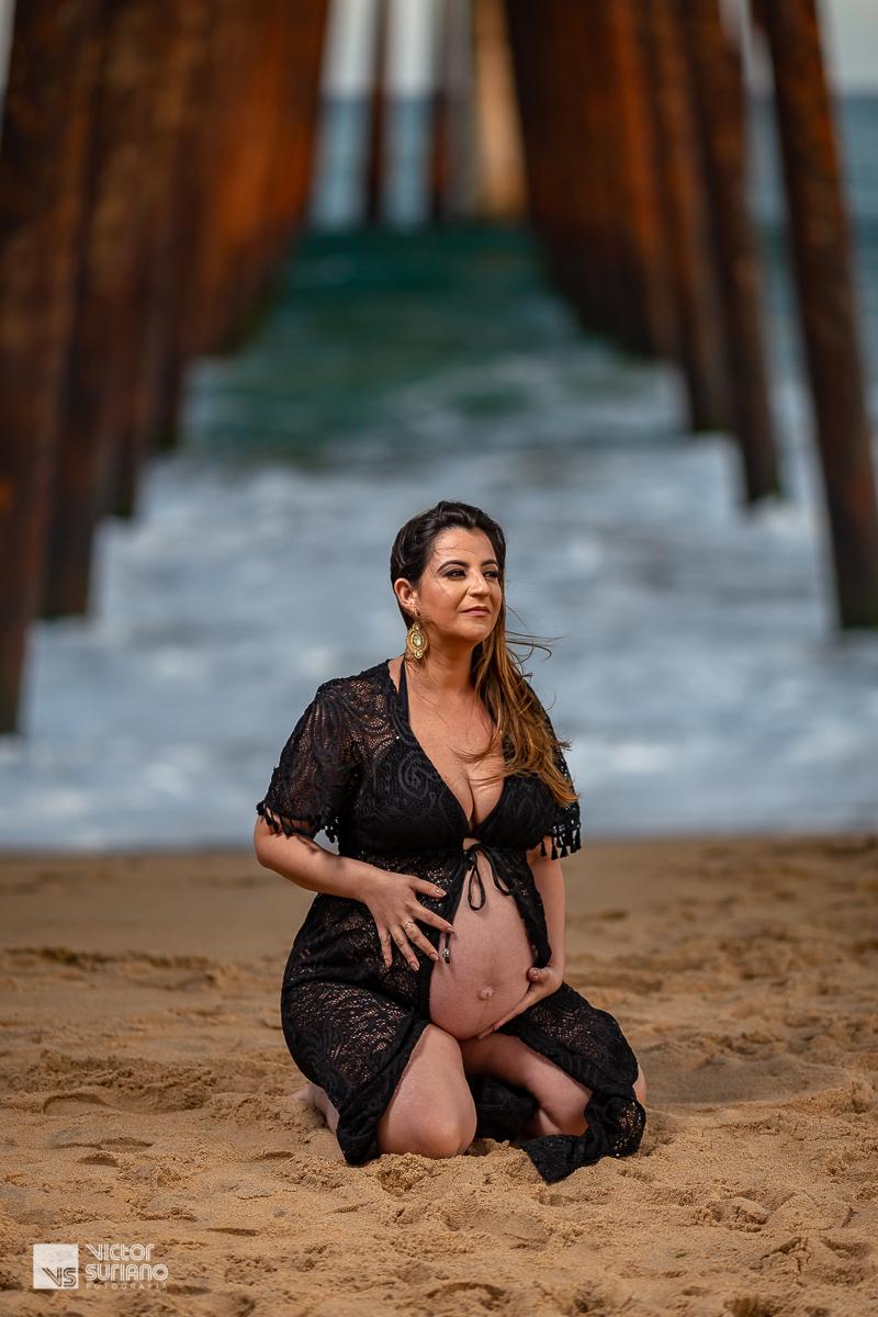 gravida com vestido preto ajoelhada na beira da praia em rio das ostras
