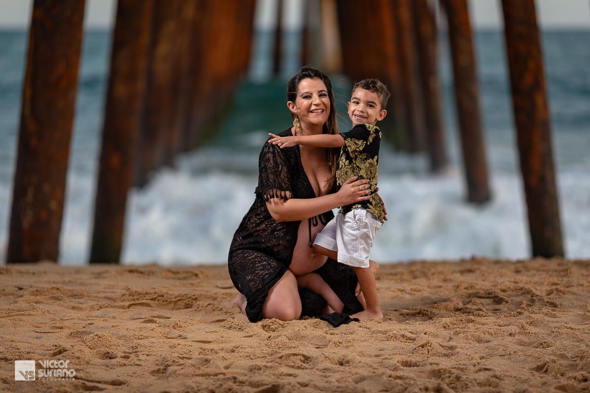 mamãe e filho abraçados na beira da praia