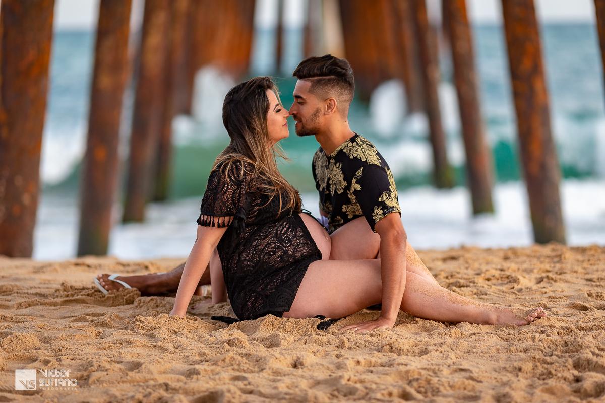 casal se beijando na beira da praia em rio das ostras vestido preto pier