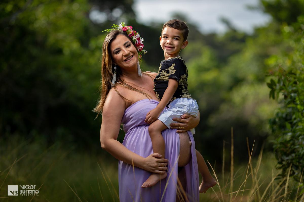 gestante com o filho no colo vestido lilás sorrindo