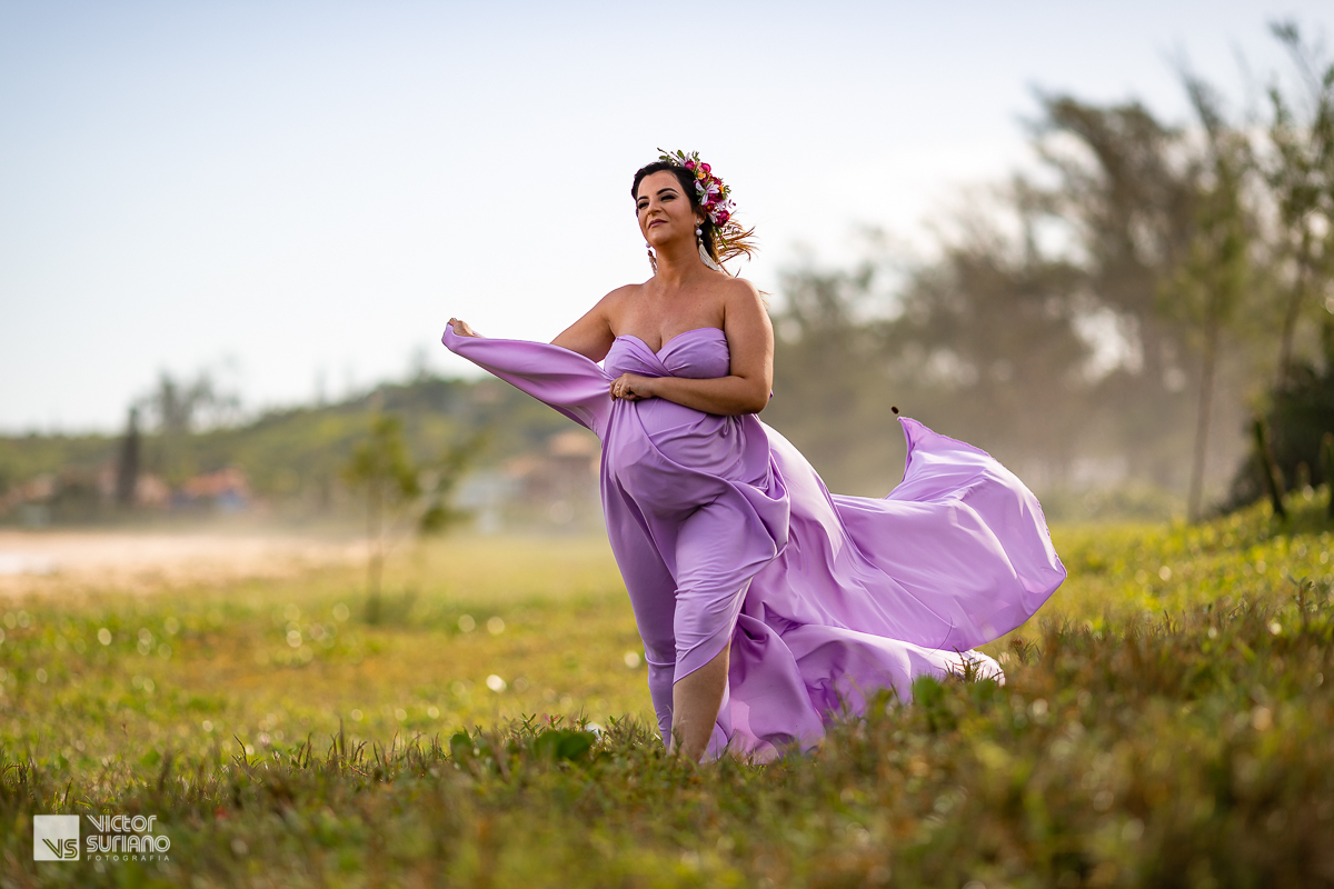 loira gestante caminhando segurando vestido lilás