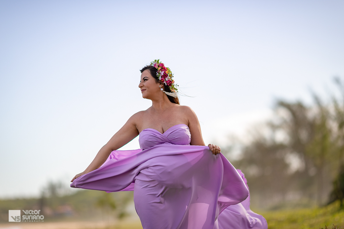 gestante olhando para o lado e balançando o vestido lilás