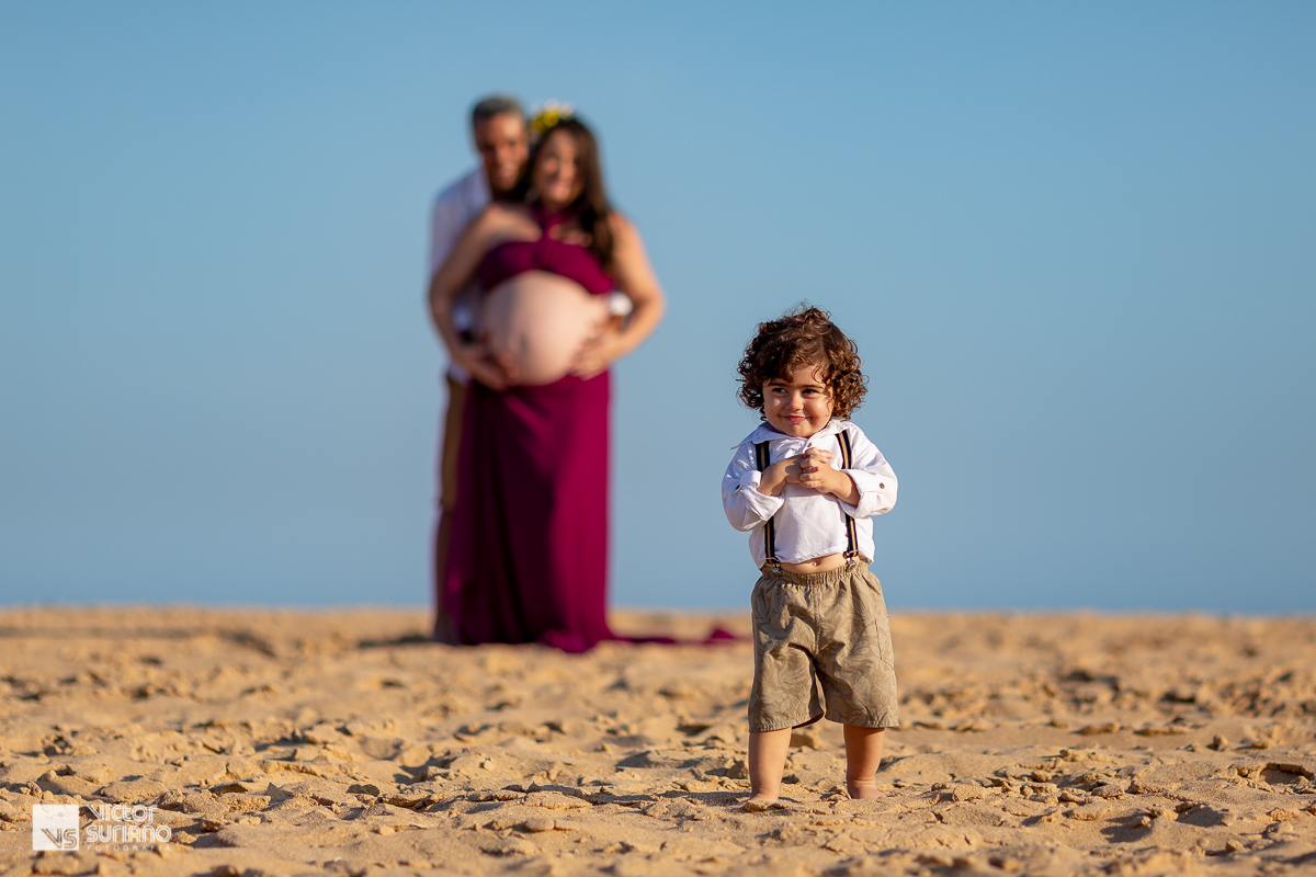 foto de bebê caminhando na areia da praia do pecado em Macaé com mamãe grávida abraçada ao papai no plano de fundo fotográfico em ensaio gestante diferente.