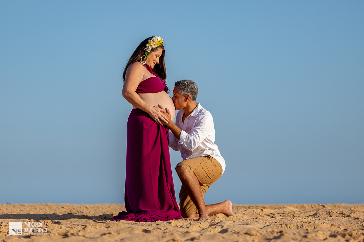 ensaio gestante diferente na beira da praia do pecado em Macaé com papai vestindo bermuda e camisa beijando a barriga da mamãe gestante que está vestindo top e saia na cor uva.