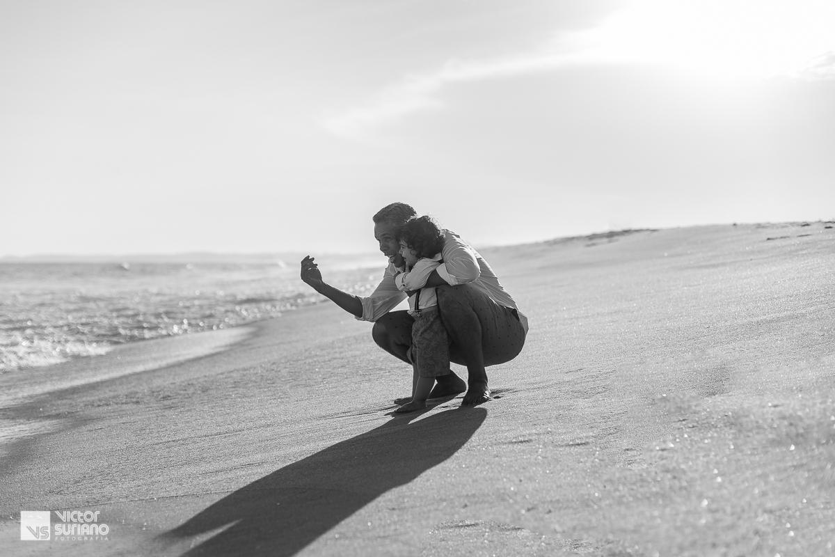fotografia em preto e branco de ensaio gestante diferente com pai e filho abraçados e brincando na beira da praia do pecado em Macaé em lindo pôr do sol