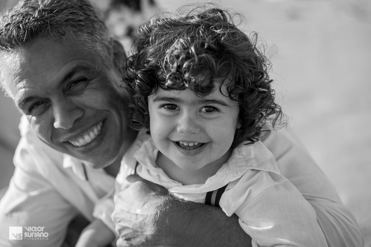 Ensaio gestante com pai e filho em foto preta e branca abraçados e com filho sorrindo olhando para a câmera.