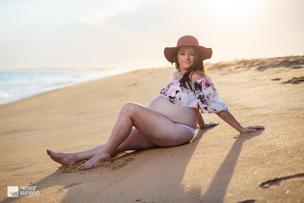 ensaio fotográfico de gestante com grávida sentada na areia da praia em Macaé e um lindo pôr do sol.