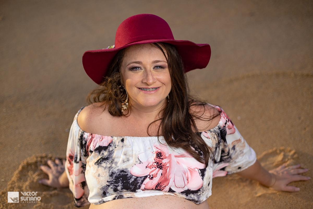 gravida sentada na areia da praia olhando para o alto e para a câmera em ensaio gestante em Macaé. ensaio gestante na beira da praia. grávida usando chapéu colorido. chapéu cor vinho