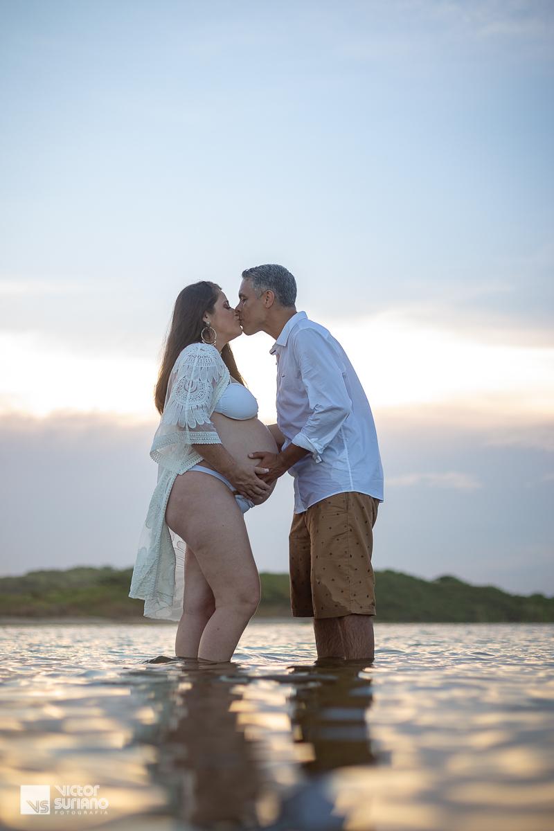 ensaio gestante com casal se beijando dentro da água na lagoa Imboassica.em Macaé.