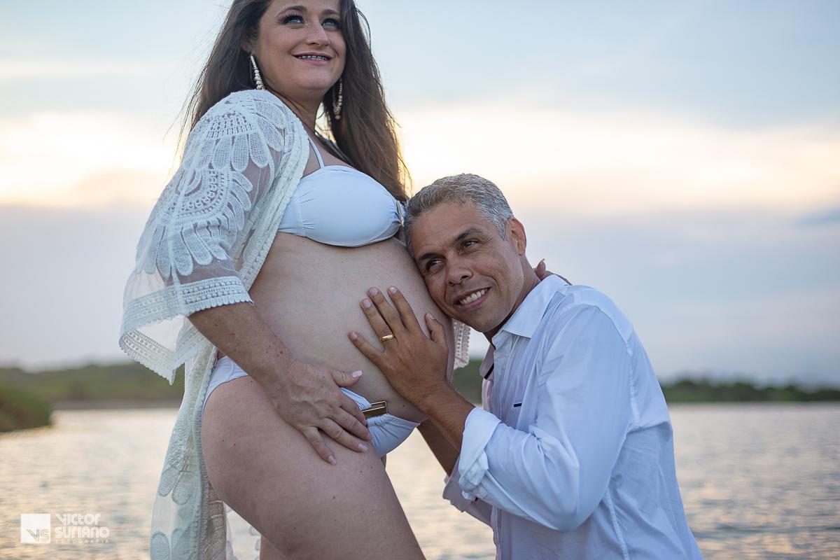 ensaio gestante com marido ajoelhado sorrindo fazendo carinho na barriga da esposa grávida dentro da água em Macaé.