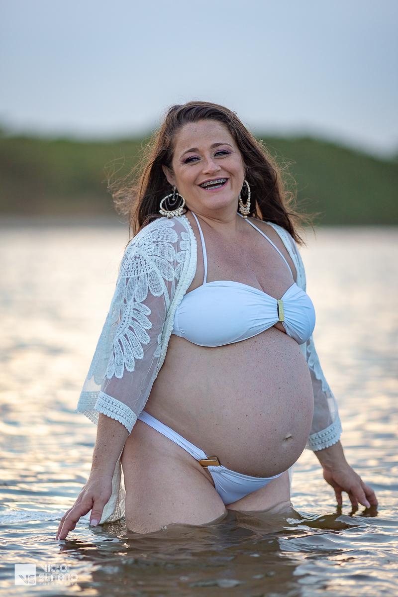 ensaio gestante na praia do pecado em Macaé com grávida usando biquini e capa branca sorrindo ensaio gestante na praia. grávida com biquini branco e capa branca.