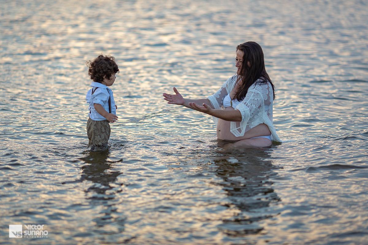 ensaio gestante na praia do pecado em Macaé com mãe e filho dentro da água e correndo para se abraçarem.