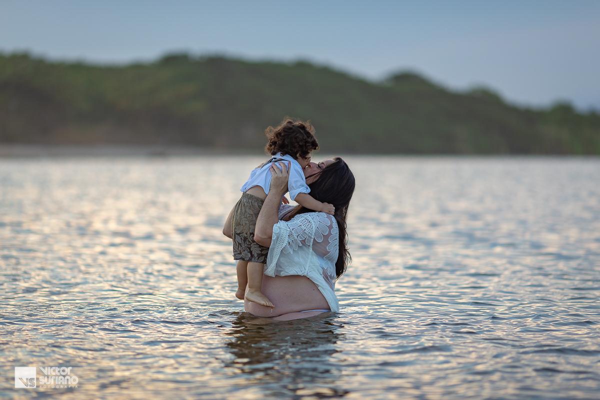ensaio gestante diferente com grávida beijando o filho no rosto dentro da água.