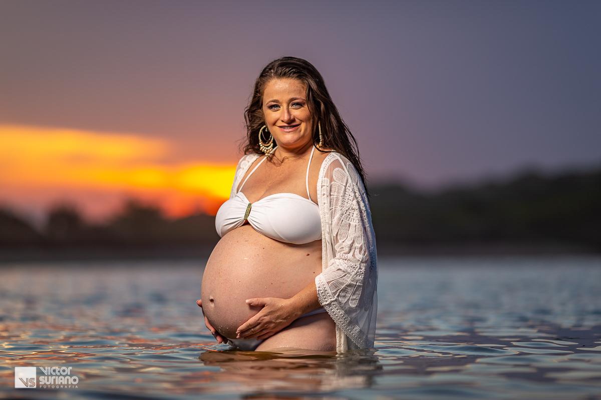 ensaio gestante na praia do pecado em Macaé com grávida acariciando a barriga em um lindo pôr do sol e dentro da água.