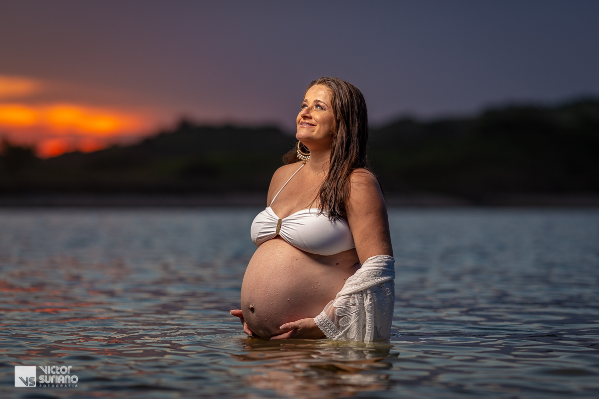 retrato de grávida dentro da água olhando para o alto em ensaio gestante diferente na beira da praia do pecado em Macaé.