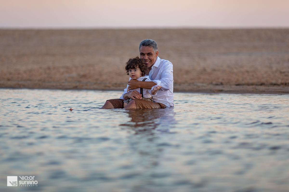 ensaio gestante na praia com pai e filho brincando e olhando para a mamãe grávida dentro da água.