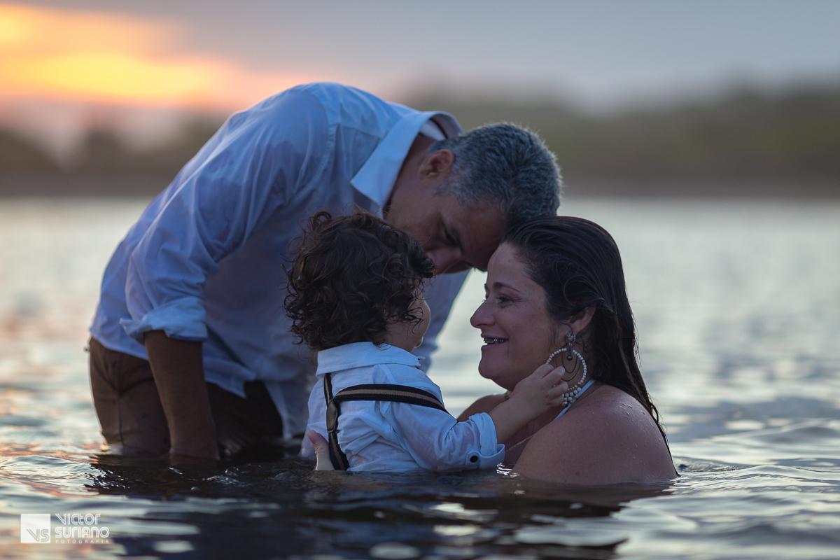 ensaio gestante na praia com família brincando dentro da água.