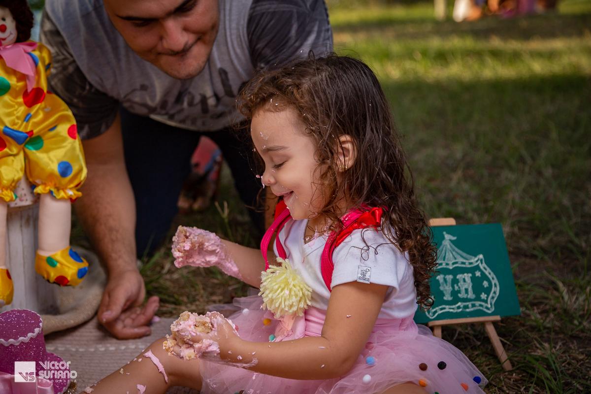 papai brinca de comer bolo com a filha em ensaio smash the cake tema circo rosa na beira do rio