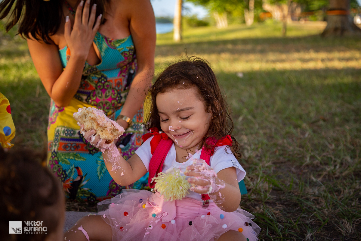 menina sorri ao suja as mã com bolo rosa do ensaio fotográfico smash the cake tema circo rosa em barra de são João.