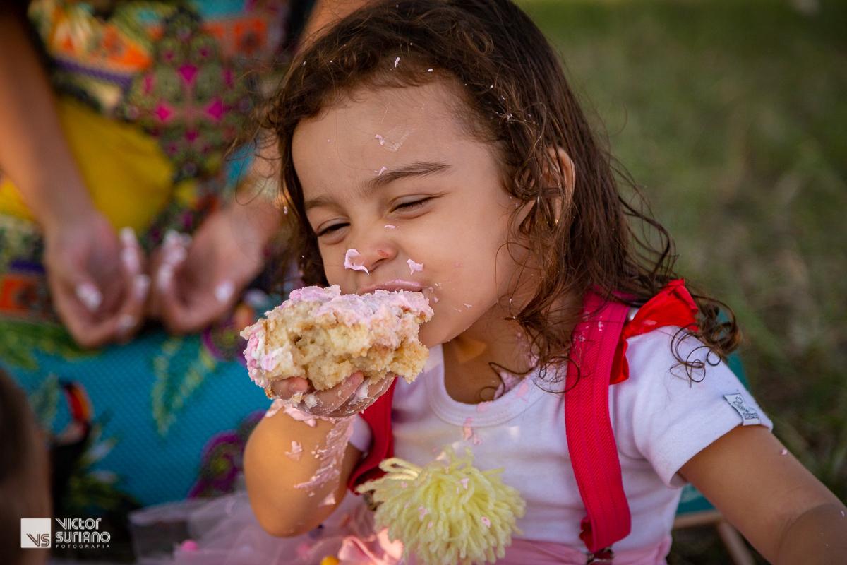 menina se suja ao comer bolo rosa em ensaio fotográfico smash the cake tema circo rosa