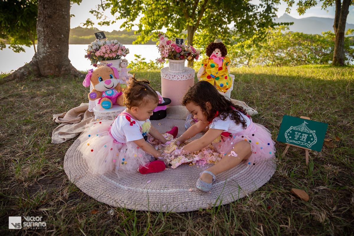 irmãs brincando com bolo rosa e se sujando em ensaio smash the cake com tema circo rosa