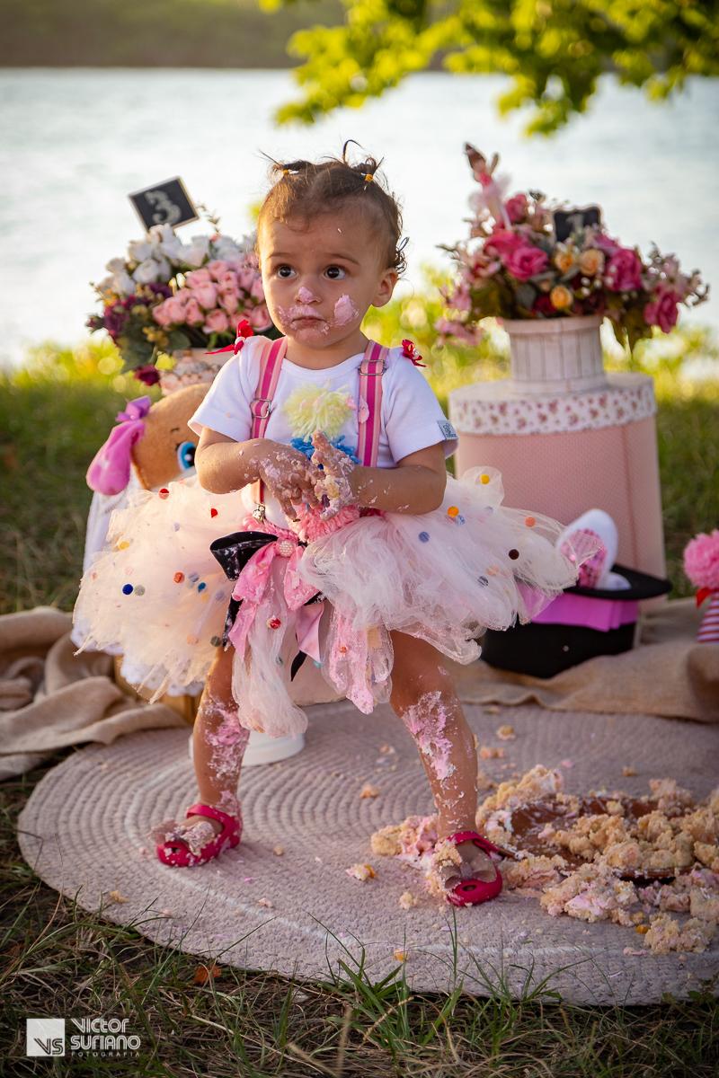 menina de um aninho em pé toda suja de bolo rosa após ensaio fotográfico smash the cake na beira do rio em barra de são João