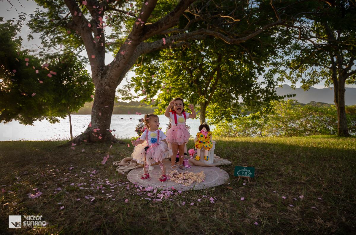 ensaio fotográfico smash the cake com irmãs sujas em pé de fazendo bagunça com papéis picados e jogados para o alto.