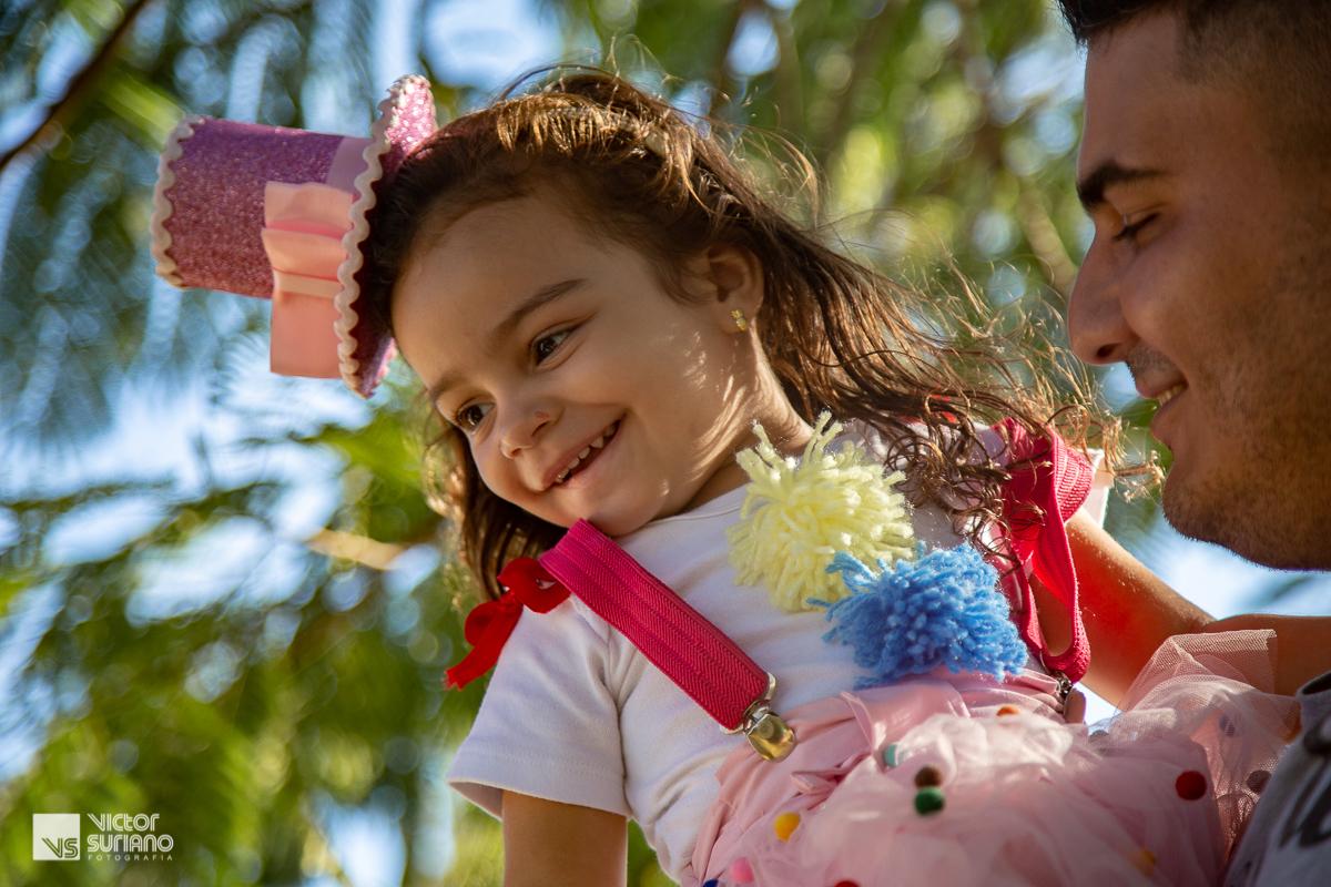 pai sorridente brincando com a filha no colo, que está usando saia rosa, pompons coloridos presos na camisa branca e suspensório rosa escuro com mini cartola rosa presa no cabelo.