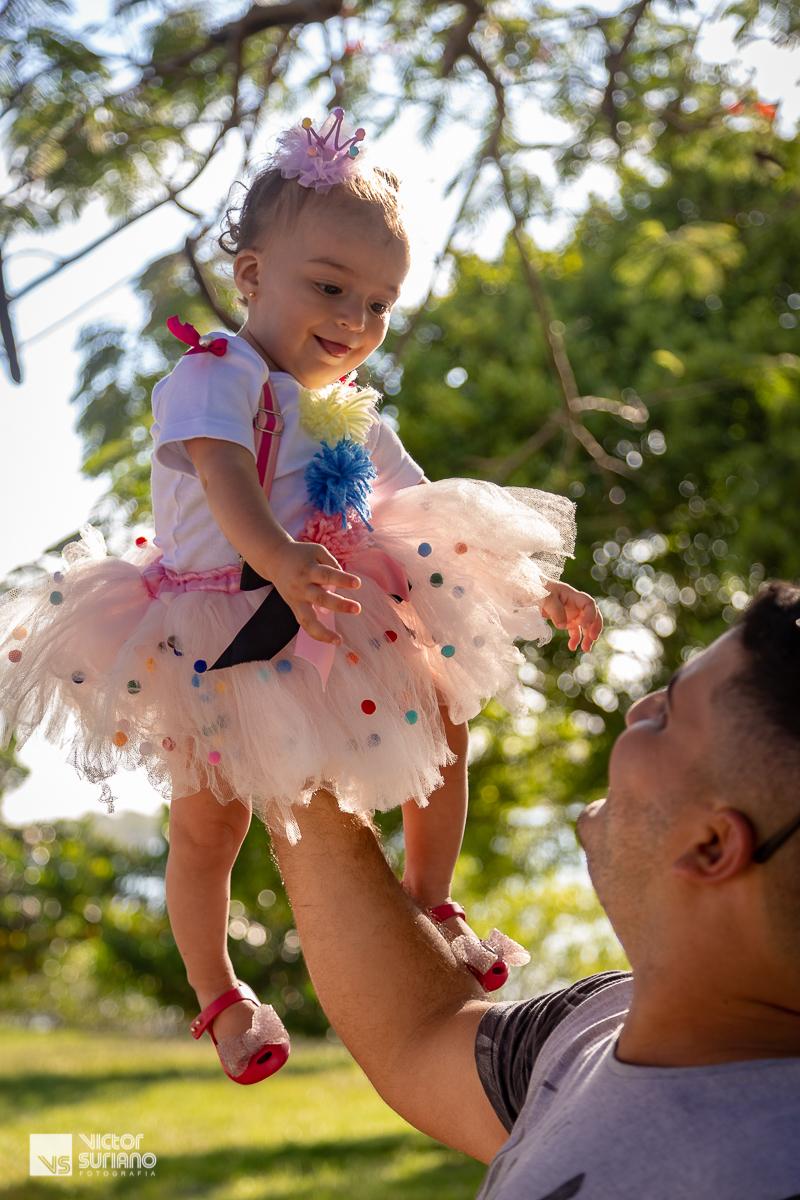 papai segurando a filha pela pernas e levantando bem alto para brincar com a menina que sorri para ele.