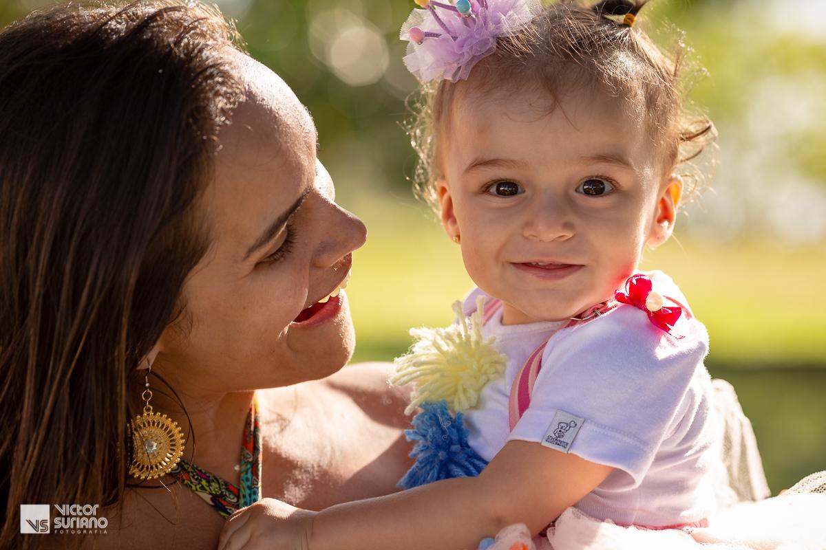 mãe sorrindo ao olhar para a filha que segura no colo e que usa laço de fita lilás na cabeça que sorri ao ver a câmera fotográfica