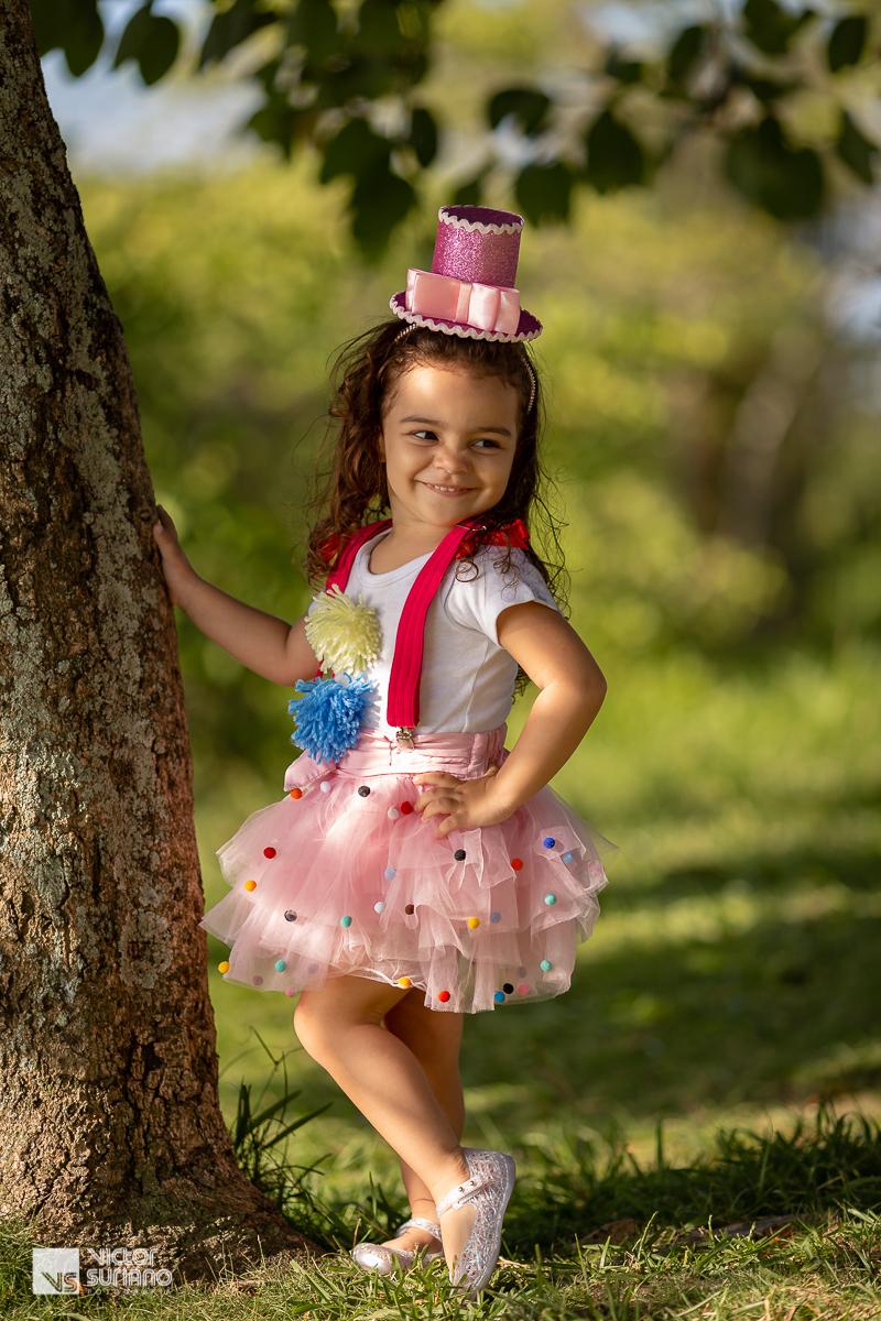 menina usando sai rosa com bolinhas de pano colorida, camisa branca com pompons na cor azul e amarelo, suspensório rosa escuro e mini cartola rosa na cabeça, fazendo pose para o fotógrafo e sorrindo para os pais.