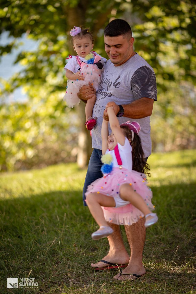papai brincando de girar com as filhas no colo em gramado verde na beira do rio em barra de são joão.