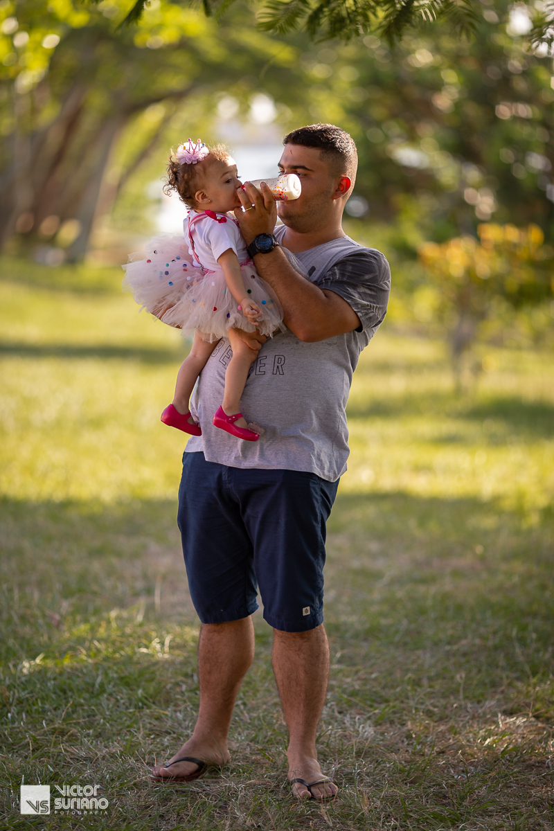 papai com filha no colo dando mamadeira com carinho para filha que usa saia rosa, camisa branca e suspensório rosa escuro.