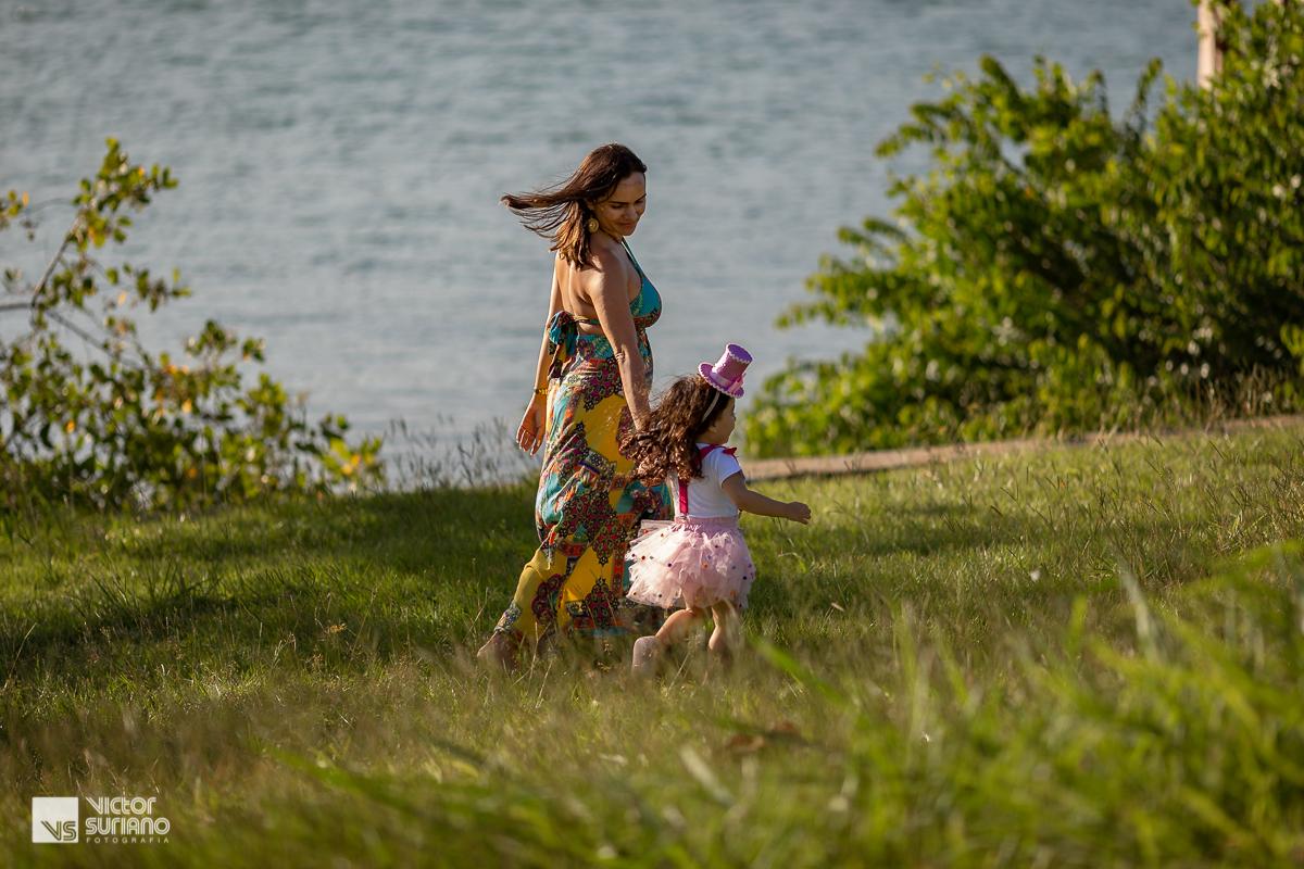 mamãe e filha correndo pelo gramado verde, de mãos dadas na beira do rio em barra de são joão.