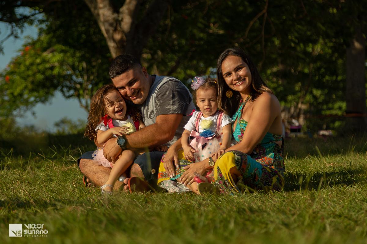 família sentada na grama, brincando e sorrindo em lindo pôr do sol na  beira do rio antes do ensaio fotográfico smash the cake