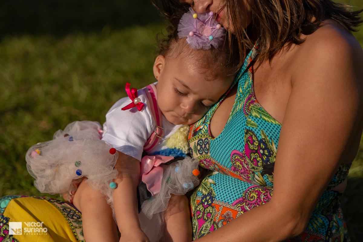 momento de carinho da mãe com a filha que está em seu colo de olhos fechados e usando saia rosa, camisa branca e laço de fita lilás na cabeça.