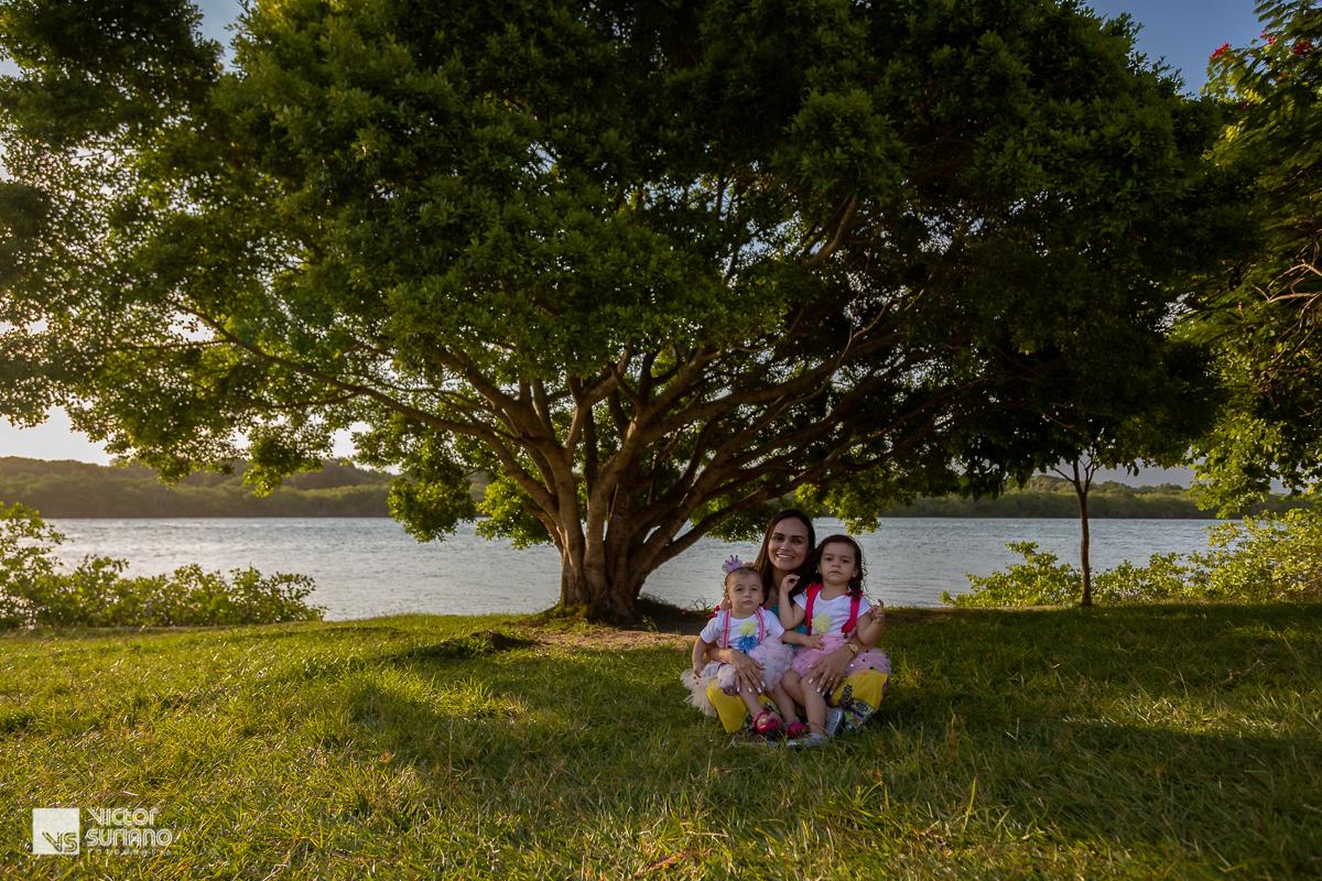 mamãe sorrindo com as filhas no colo fazendo pose para ensaio fotográfico smash the cake.