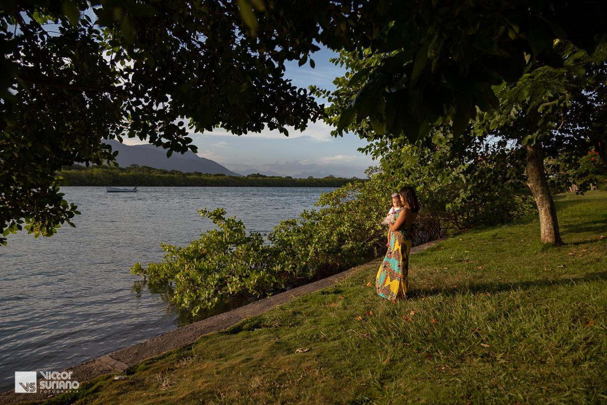 mamãe com a filha mais nova no colo olhando para o sol na beira do rio em barra de são João.