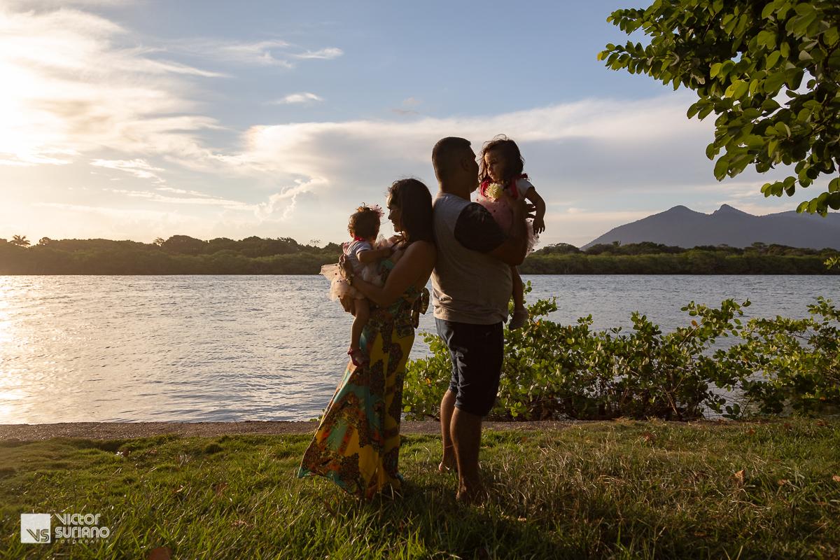 papai e mamãe de costas um para o outro segurando as filhas no colo em lindo pôr do sol na beira do rio