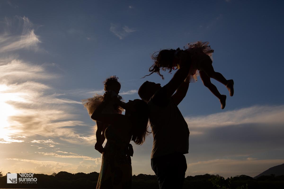 papai e mamãe brincando de jogar as filhas para o alto em lindo pôr do sol na beira do rio em barra de são João.