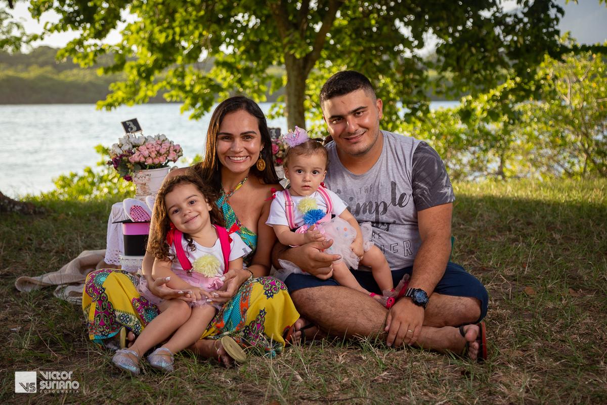 família sorrindo para a câmera fotográfica em ensaio smash the cake na beira do rio com tema circo rosa
