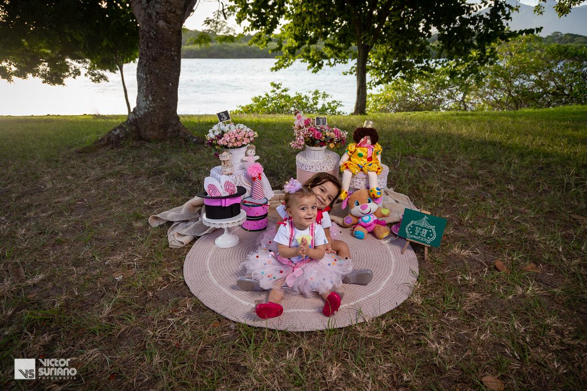 irmãs abraçadas e sentada em tapete de crochê lilás em ensao smash the cake com tema circo rosa realizado em barra de são João.
