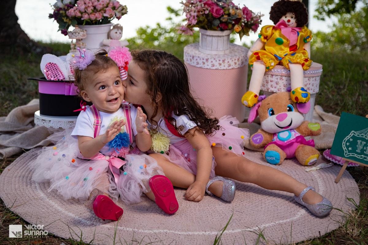 irmã mais velha dá beijo no rosto da mais nova que sorri para os papais em ensaio smash the cake com tema circo rosa.
