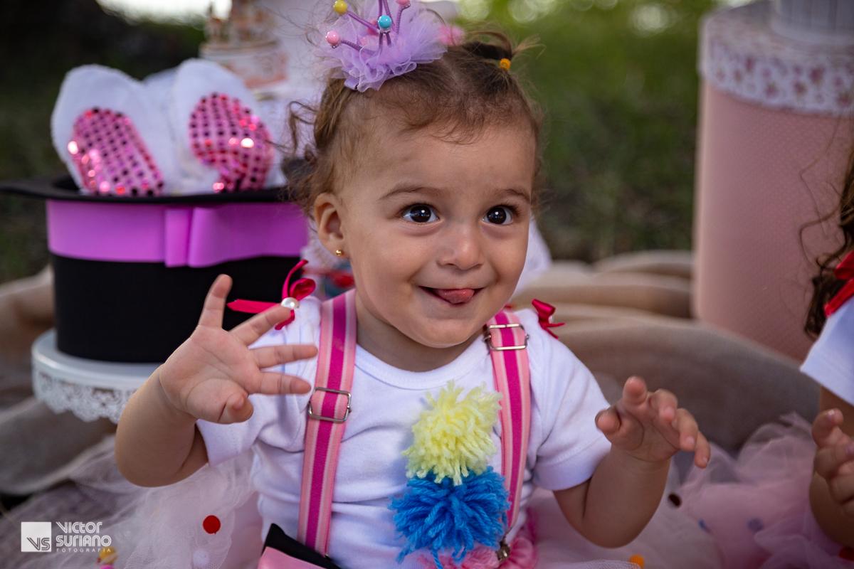 menina usando saia rosa camisa branca e suspensório rosa escuro e laço de fita na cabeça sorrindo e com a língua para fora brincando com a mamãe em ensaio smash the cake