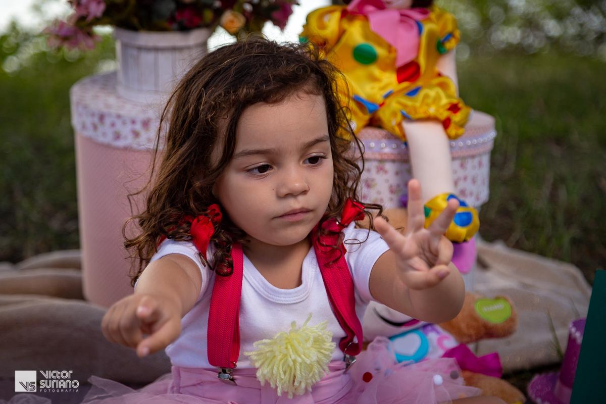 menina fazendo com as mão os números um e três em cenário fotográfico com tema circo rosa para ensaio smash the cake