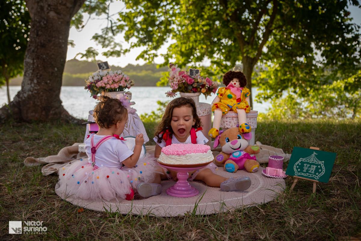 irmã mais velha com a boca aberta para comer o bolo rosa confeitado e a mais nova  brincando com enfeitas da decoração do cenário do ensaio fotográfico smash the cake no tema circo rosa