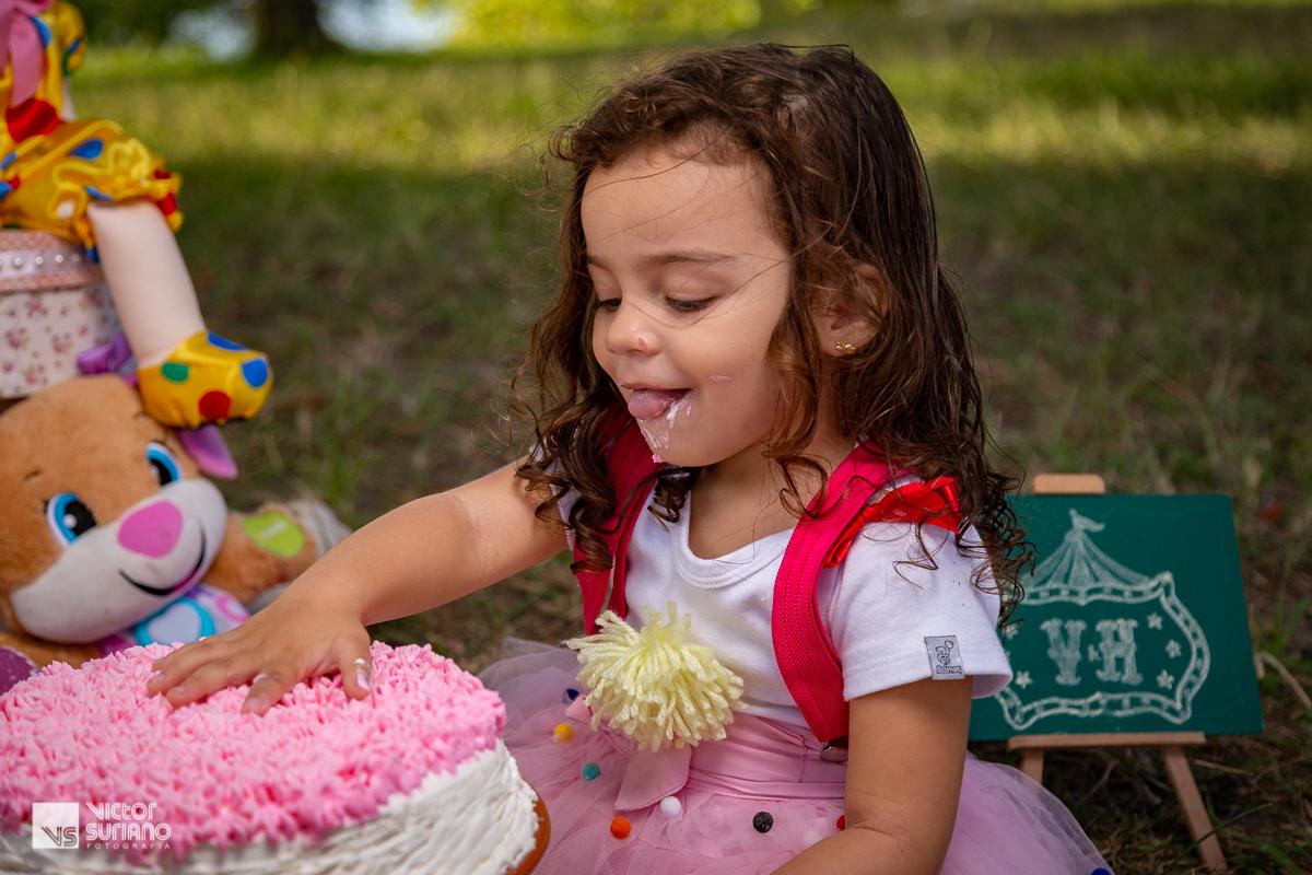 menina sorrindo bate a mão em cima de bolo em ensaio fotográfico smash the cake tema circo rosa